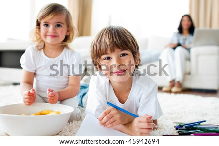 Smiling siblings eating chips and drawing lying on the floor - stock photo