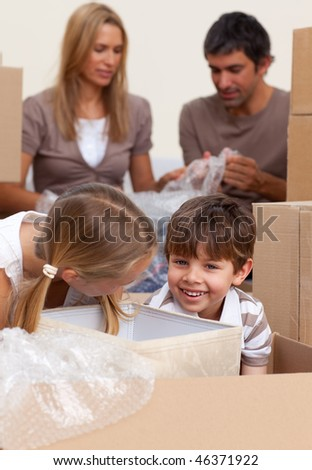 Smiling siblings having fun during house moving at home - stock photo