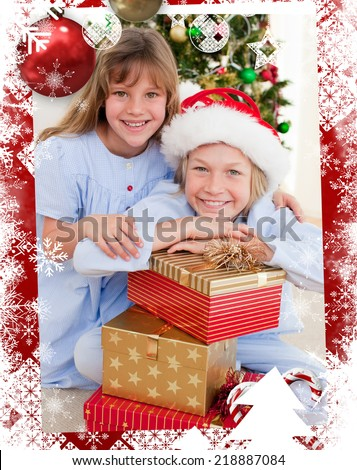 Smiling siblings holding Christmas gifts against christmas themed frame - stock photo