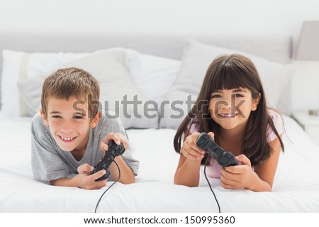 Smiling siblings lying on bed playing video games together at home - stock photo