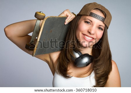 Smiling skater girl holding skateboard - stock photo