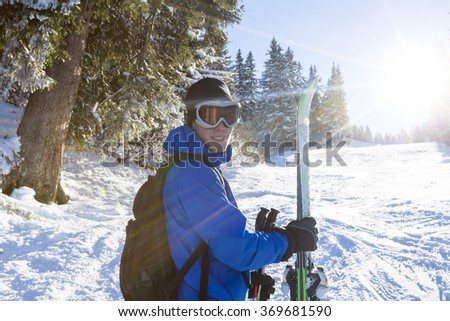 Smiling skier standing near the forest with ski in hand, sunny day - stock photo