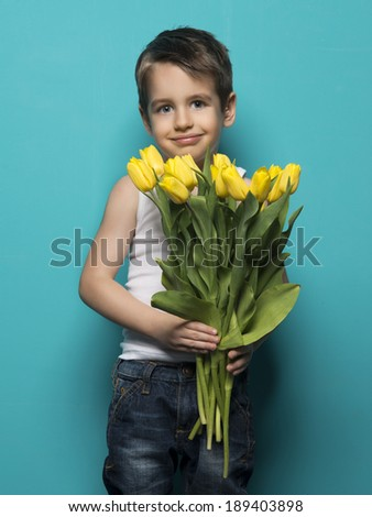 Smiling small boy with  yellow tulip .  International Womens, Mothers day - stock photo