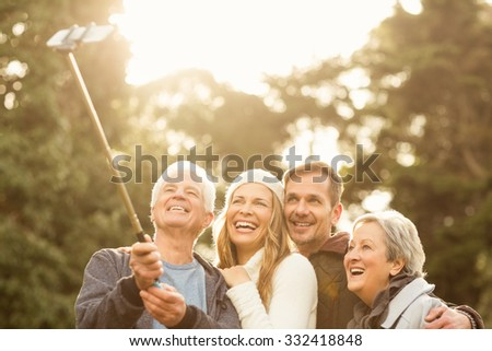 Smiling small family taking selfies on an autumns day - stock photo