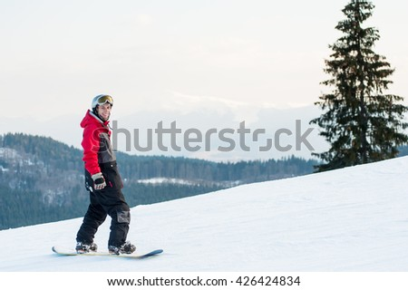 Smiling snowboarder wearing helmet, red jacket, gloves and pants standing on top of a mountain and looking at the camera near a lonely pine on the background of hills and the sky tightened white cloud