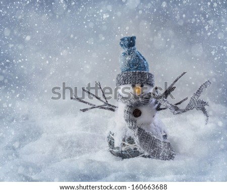 Smiling snowman standing in the snow - stock photo