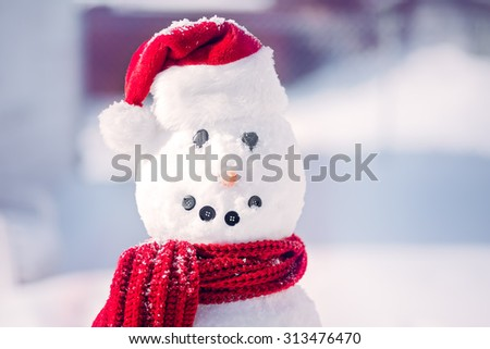 Smiling snowman with red santa hat and scarf - stock photo