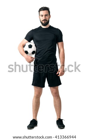 Smiling soccer or futsal player wearing black sportswear holding ball under his arm looking at camera. Full body length portrait isolated over white background.  - stock photo