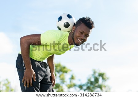 Smiling soccer player balancing ball on his neck - stock photo