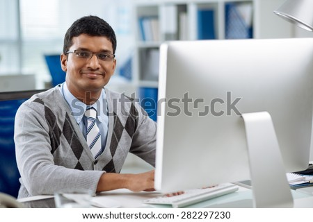 Smiling software developer working on computer - stock photo