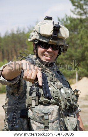 Smiling soldier holding his pistol - stock photo