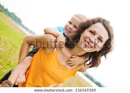 Smiling son enjoying a piggyback ride on his mothers back - stock photo
