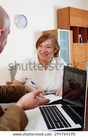 Smiling son helping senior mother to buy apartment - stock photo