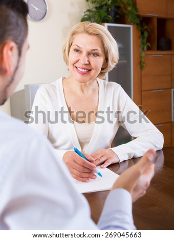 Smiling son helping senior mother with documents for buying apartment