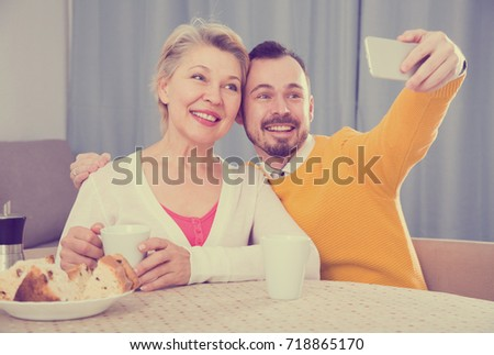 Smiling son with his mature mother doing selfie at home at table