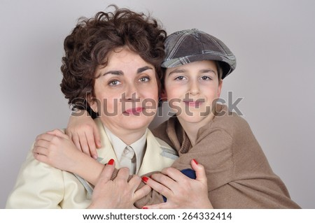 Smiling son with tartan newsboy cap hugging his smiling mother. Isolated on the gray background. Vintage style photo - stock photo