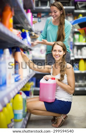 smiling spanish people buying detergents for house in the shopping mall