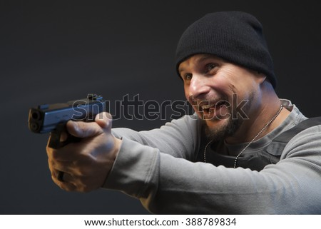 Smiling Special Agent with weapon, giving the impression he may be unstable.  Studio shoot of officer who might be a loose cannon or crazy. Focus is on the officer's face and not the weapon. - stock photo