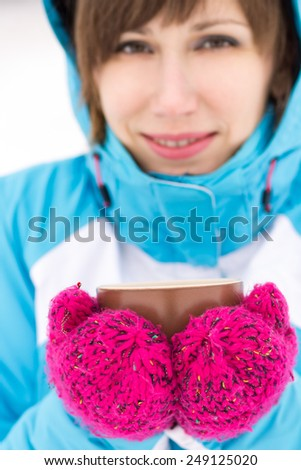 Smiling sport woman holding cup of hot tea or coffee at winter outdoor - stock photo