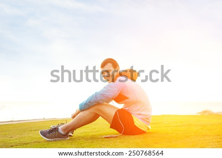 smiling sportsman sitting on the grass in the park and listening music on his phone - stock photo