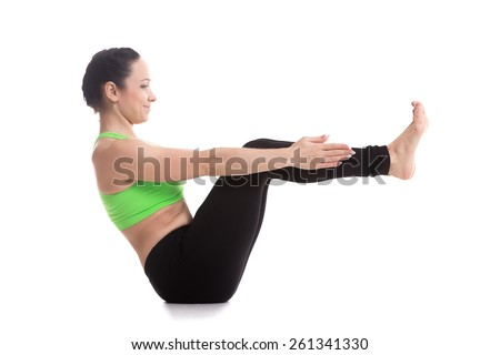 Smiling sporty beautiful girl practices yoga, sitting in boat pose, Navasana, strengthens abdomen, hip flexors, spine, flat belly - stock photo