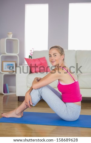 Smiling Sporty Blonde Model Sitting On Blue Exercise Mat In Bright Living Room