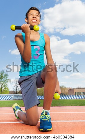 Smiling sporty boy with dumbbells on the stadium