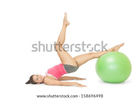 Smiling sporty brunette exercising with exercise ball on white background - stock photo