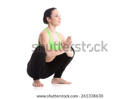 Smiling sporty girl on white background sitting in Garland yoga Pose, Malasana, yoga for stretching ankles, groins, back, strengthening belly, hands in Anjali Mudra (Salutation Seal) - stock photo