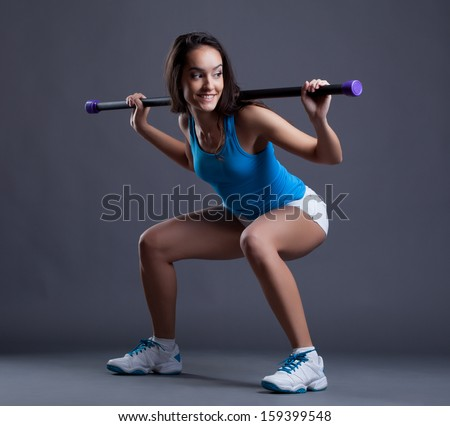 Smiling sporty woman crouches with fitbar - stock photo