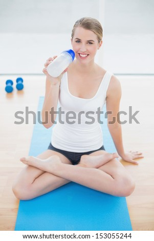 Smiling sporty woman in lotus position in bright sports hall drinking water - stock photo