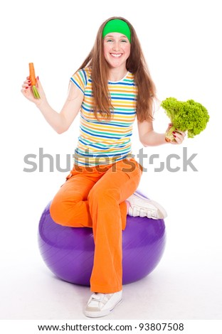 Smiling sporty woman on ball with heathy food at hands - stock photo