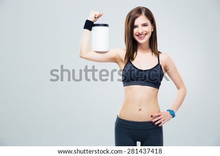 Smiling sporty woman with jar of protein on hand over gray background and looking at camera - stock photo