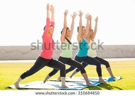 Smiling sporty women doing warrior pose in yoga class in parkland