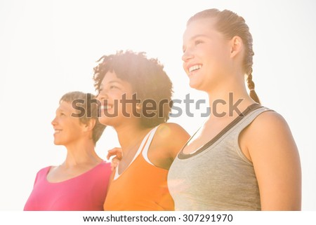 Smiling sporty women looking far away at promenade - stock photo