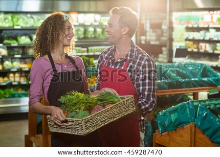 Smiling staffs holding basket of vegetable in organic section of supermarket - stock photo