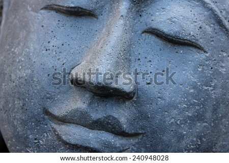 Smiling Stone Buddha Statue face with closed eyes from Indonesia looking to the left - stock photo
