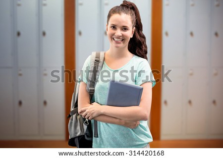 Smiling student against closed lockers in a row at the college - stock photo