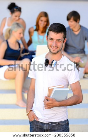 Smiling student boy  holding books friends sitting on college steps - stock photo