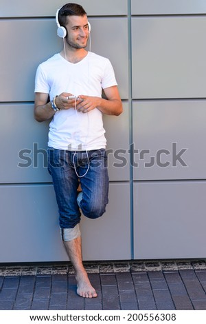 Smiling student boy with headphones leaning against modern college wall - stock photo