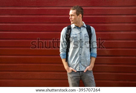 Smiling student casual dressed standing against red background, talking at cellphone and having a backpack - stock photo