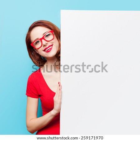 Smiling student girl in red dress and glasses with white board on blue background