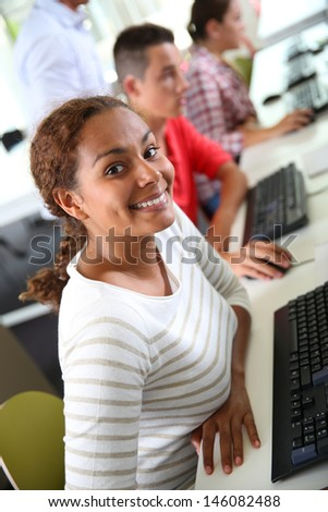 Smiling student girl sitting in computing class - stock photo