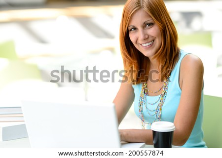 Smiling student girl with laptop at college looking at camera - stock photo