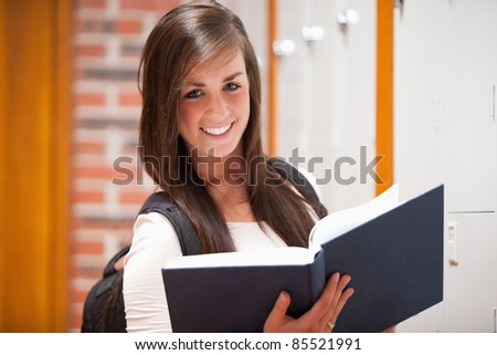 Smiling student holding a book in a corridor - stock photo