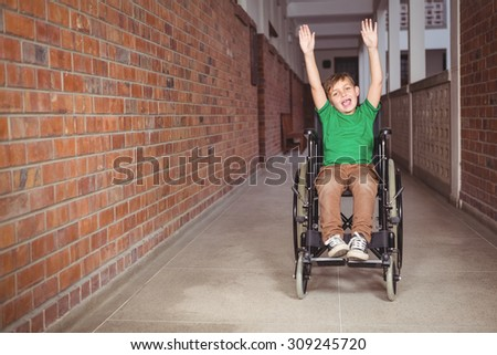 Smiling student in a wheelchair with arms raised on the elementary school grounds - stock photo