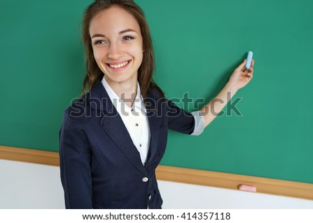 Smiling student or teacher standing in front of the blank blackboard with piece of chalk in her hand. Education concept