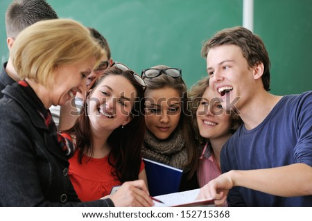 Smiling student pointing to his teacher's book - stock photo
