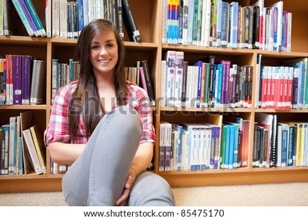 Smiling student sitting against shelves in a library