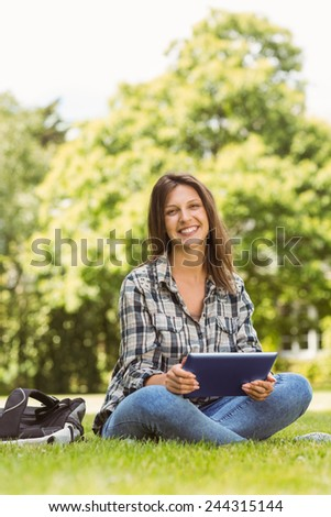 Smiling student sitting and using tablet pc in park at school - stock photo
